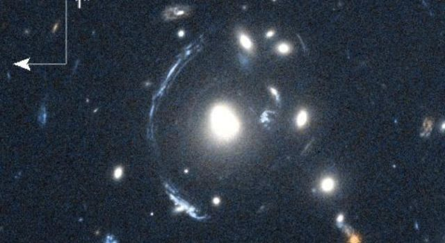 The young galaxy SDSS090122.37+181432.3, also known as S0901, is seen here by the Herschel Space Observatory and the Hubble Space Telescope as the bright arc to the left of the central bright galaxy.