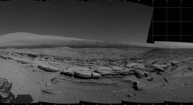 "This view from NASA's Curiosity Mars rover spans 360 degrees, centered southward toward a planned science waypoint at ""the Kimberley,"" with an outcrop of eroded sandstone in the foreground."