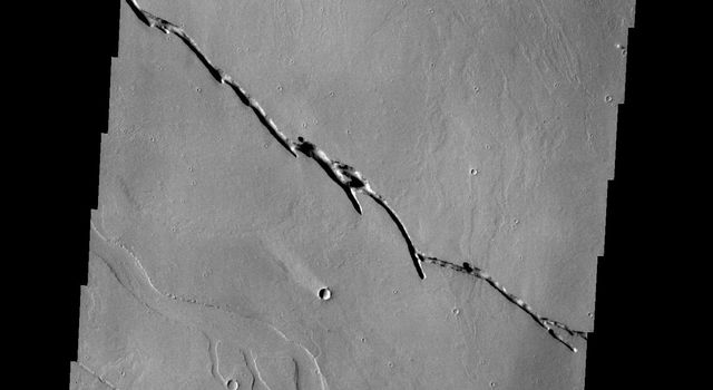 This image from NASA's 2001 Mars Odyssey spacecraft shows a small region between Olympus Mons and Sulci Gordii. There are lava flows, tectonic depressions and channels visible in the image. All the features are related to the volcanism.