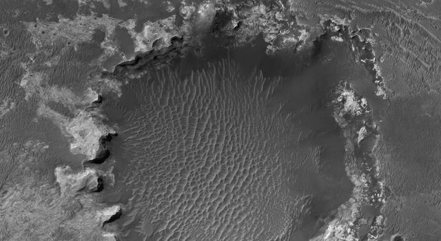 NASA's Mars Reconnaissance Orbiter spies an impact crater located in northern Sinus Meridiani has formed along the boundary of two different terrain units.