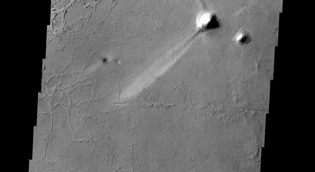 A long, narrow windstreak has formed in the lee of this hill in the Tartarus Montes. Several small dark craters also have windstreaks as shown by NASA's 2001 Mars Odyssey spacecraft.