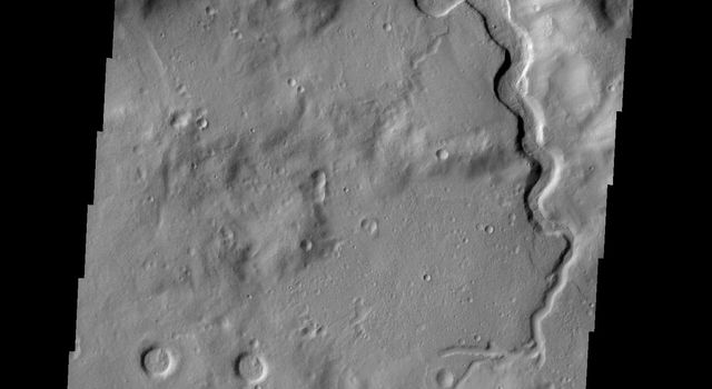 This image from NASA's 2001 Mars Odyssey spacecraft shows an unnamed channel that dissects the rim of a large crater in Arabia Terra.