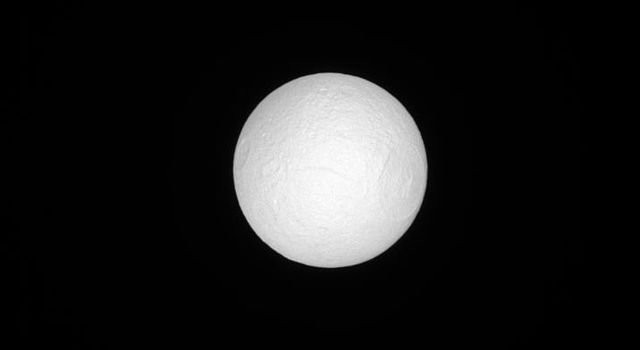 Seen by NASA's Cassini spacecraft, Tethys, like many moons in the solar system, keeps one face pointed towards the planet around which it orbits. Tethys' anti-Saturn face is seen here, fully illuminated, basking in sunlight.
