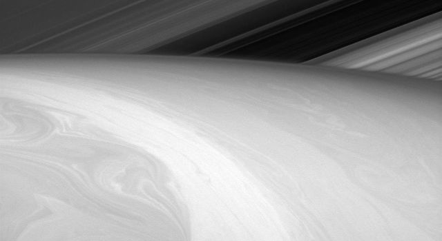 Nature is an artist, and this time she seems to have let her paints swirl together a bit. What the viewer might perceive to be Saturn's surface captured by NASA's Cassini orbiter is really just the tops of its uppermost cloud layers.