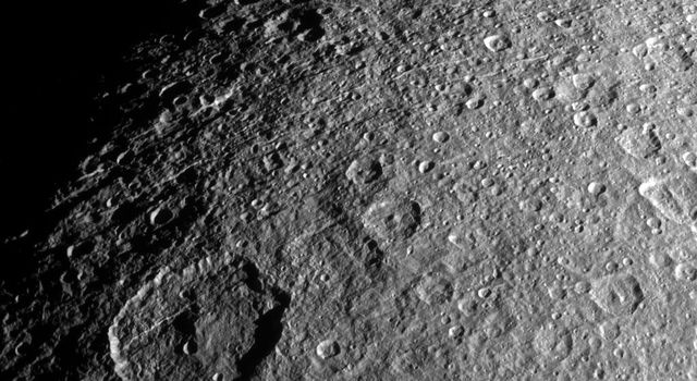Surface features on Rhea, mostly impact craters in this image from NASA's Cassini spacecraft, are thrown into sharp relief thanks to long shadows.