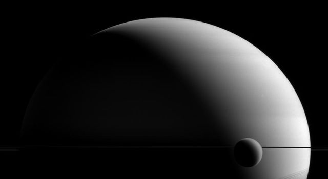 Titan and Saturn share a hazy appearance in this image from NASA's Cassini spacecraft, though Saturn is a gas giant with no solid surface to speak of, and Titan's atmosphere is a blanket surrounding an icy, solid body.