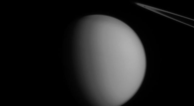 A coincidence of viewing angle makes Pandora appear to be hovering over Titan, almost like an accent mark, in this image from NASA's Cassini spacecraft.