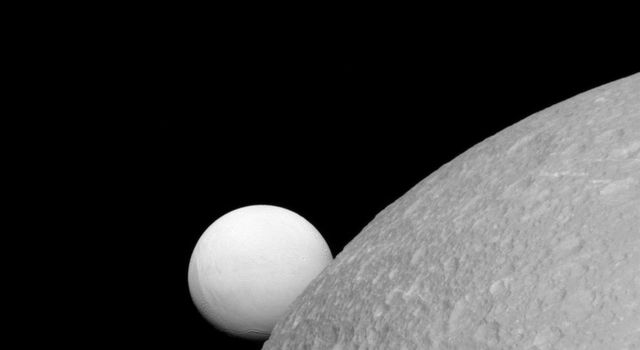 Although Dione (near) and Enceladus (far) are composed of nearly the same materials, Enceladus has a considerably higher reflectivity than Dione. As a result, it appears brighter against the dark night sky as seen by NASA's Cassini spacecraft.