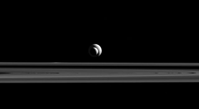 Like a cosmic bull's-eye, Enceladus and Tethys line up almost perfectly for NASA's Cassini. Since they are also at relatively similar distances from the spacecraft, their apparent sizes in this image are a good approximation of their relative sizes.