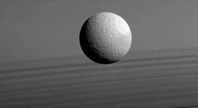 Saturn's moon Tethys appears to float between two sets of rings in this view from NASA's Cassini spacecraft, but it's just a trick of geometry. The rings, which are seen nearly edge-on, are the dark bands above Tethys.