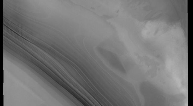 This image captured by NASA's 2001 Mars Odyssey spacecraft shows the layering of the north polar cap. Such layering is visible on the sides of troughs carved into the ice.