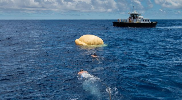 Hours after the June 28, 2014, test of NASA's Low-Density Supersonic Decelerator over the U.S. Navy's Pacific Missile Range, two members of the Navy's Explosive Ordinance Disposal swim toward the test vehicle.