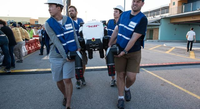 Engineers from NASA's Jet Propulsion Laboratory carry RoboSimian, a robot developed at JPL, at the DARPA Robotics Challenge Trials in Florida in December 2013.