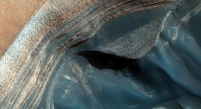 The North Polar layered deposits (NPLD) are a stack of layers of ice and dust at the North Pole of Mars. The layers are thought to have been deposited over millions of years. This image is from NASA's Mars Reconnaissance Orbiter.