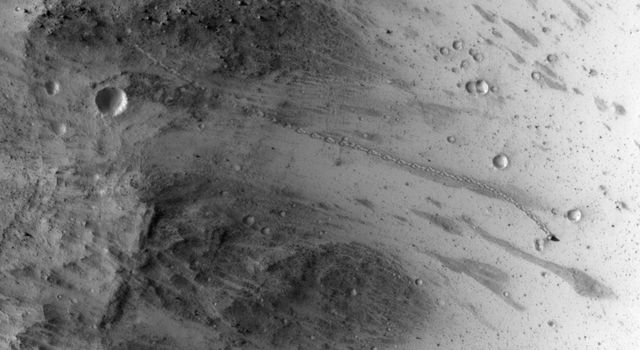 The track left by an oblong boulder as it tumbled down a slope on Mars runs from upper left to right center of this image taken by NASA's Mars Reconnaissance Orbiter.