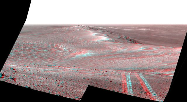 This stereo 3D scene from the Pancam on NASA's Mars Exploration Rover Opportunity looks back toward part of the west rim of Endeavour Crater that the rover drove along, heading southward, during the summer of 2014.