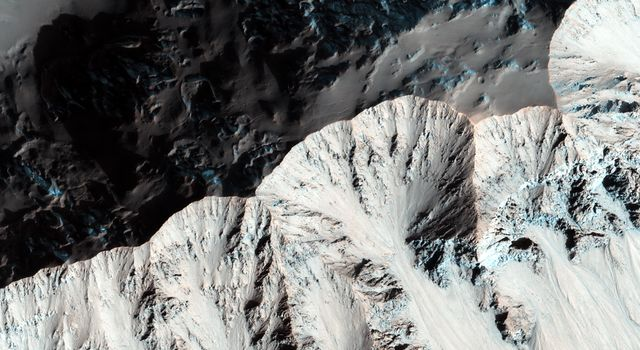 Right past the sharp, but warped rim of this ancient impact crater are deposits of winter frost, which show up as blue in enhanced color as seen by NASA's Mars Reconnaissance Orbiter.