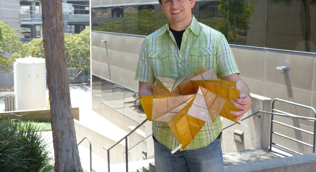 A researcher at NASA's Jet Propulsion Laboratory in Pasadena, holds a prototype of a solar panel array that folds up in the style of origami.