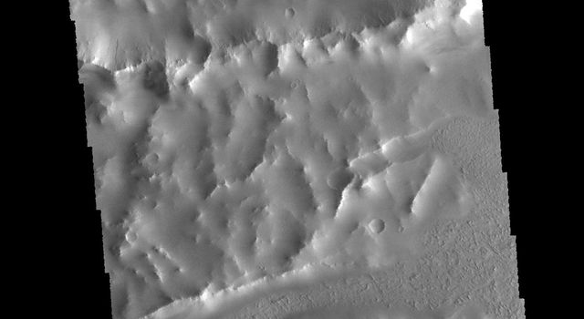Lava flows of Daedalia Planum can be seen at the top and bottom portions of this image from NASA's 2001 Mars Odyssey spacecraft. The ridge and linear depression in the central part of the image are part of Mangala Fossa, a fault bounded graben.