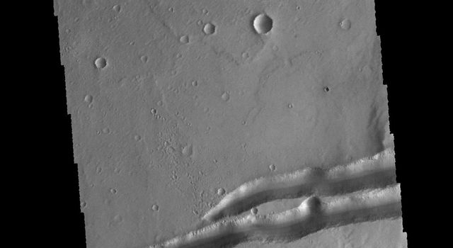 The depression in the center of this image captured by NASA's 2001 Mars Odyssey spacecraft is a graben (fault bounded block of material). This graben is called Mangala Fossa.