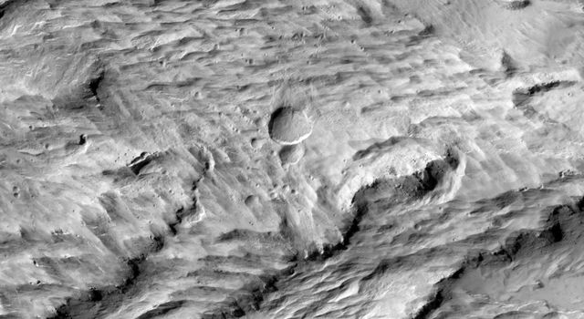 A large new crater, seen by NASA's Mars Reconnaissance Orbiter, appear slightly asymmetric in shape, and measures 159 x 143 feet (48.5 x 43.5 meters) in diameter, making it the largest new crater detected on Mars by MRO to date.