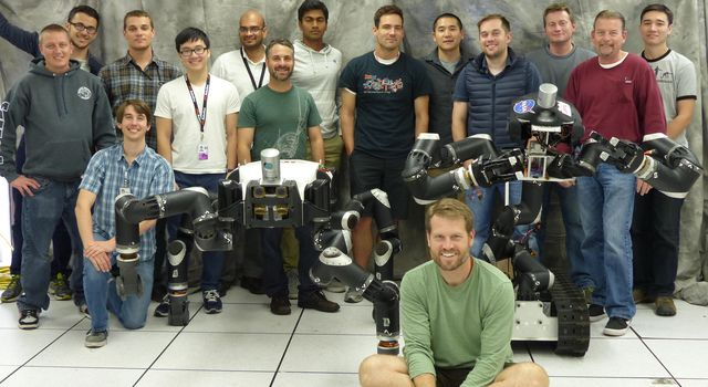Robotics researchers at NASA's Jet Propulsion Laboratory in Pasadena, California, stand with robots RoboSimian and Surrogate, both built at JPL.