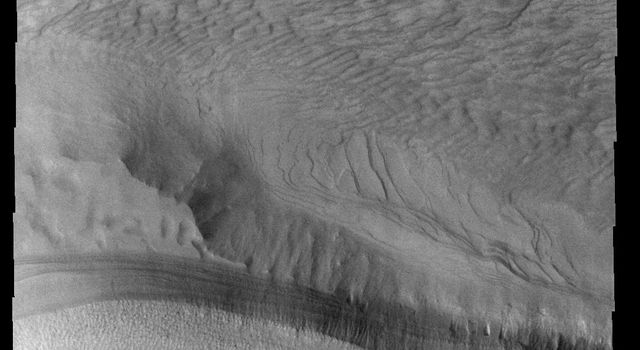 This image from NASA's 2001 Mars Odyssey spacecraft contains the margin of the south polar cap (bottom half) and dunes in an unnamed crater (top half). Part of the crater is covered by ice, which may affect the winds creating these dunes.