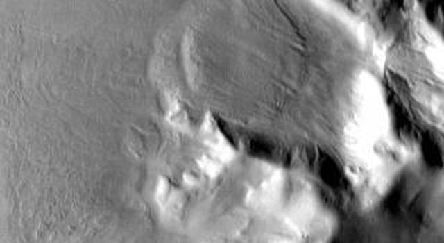 This infrared image captured by NASA's 2001 Mars Odyssey spacecraft shows bright toned material, which is warmer than dark toned surfaces. Material has moved downslope from the top of this hill in Promethei Terra.