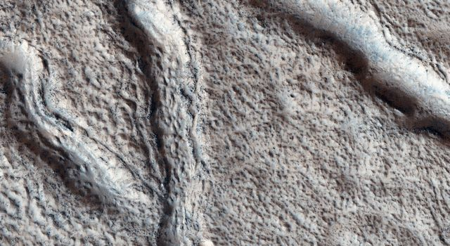 This observation from NASA's Mars Reconnaissance Orbiter shows the nature of large fissures in a smooth apron around a mound in the Phlegra region.