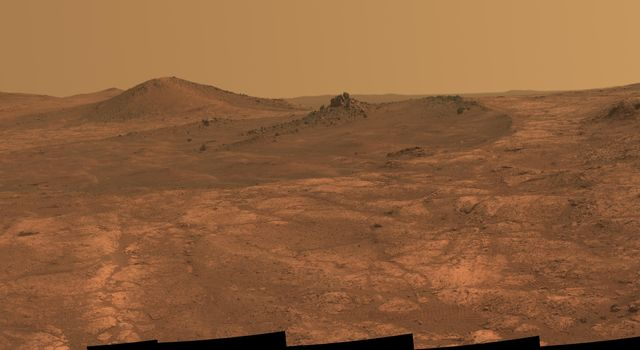 An elongated crater called 'Spirit of St. Louis,' with a rock spire in it, dominates a recent scene from the panoramic camera (Pancam) on NASA's Mars Exploration Rover Opportunity.