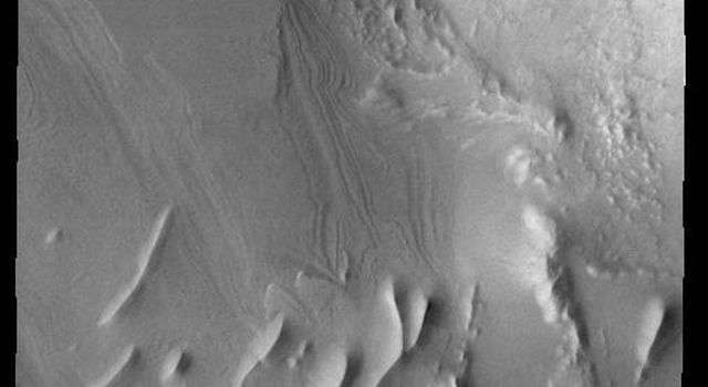 This image captured by NASA's 2001 Mars Odyssey spacecraft shows layering and linear ridges in Cavi Angusti. This region is near the south polar cap.