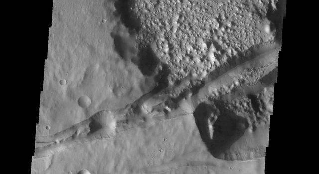 This image captured by NASA's 2001 Mars Odyssey spacecraft shows several linear depressions that cross an unnamed crater. The depressions are tectonic fractures that are hundreds of km long.