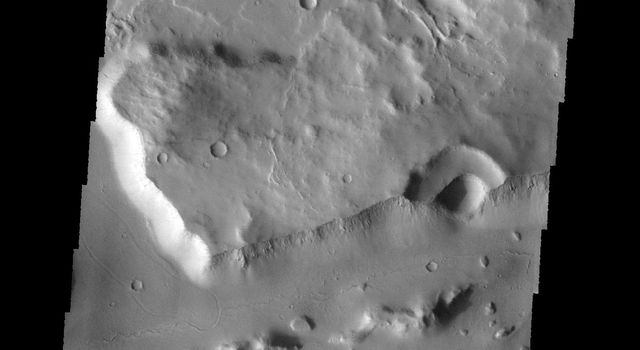 The linear wall at the bottom of this image from NASA's 2001 Mars Odyssey spacecraft is a fault. The linear depression caused by faulting is part of a long depression called Mangala Fossae.