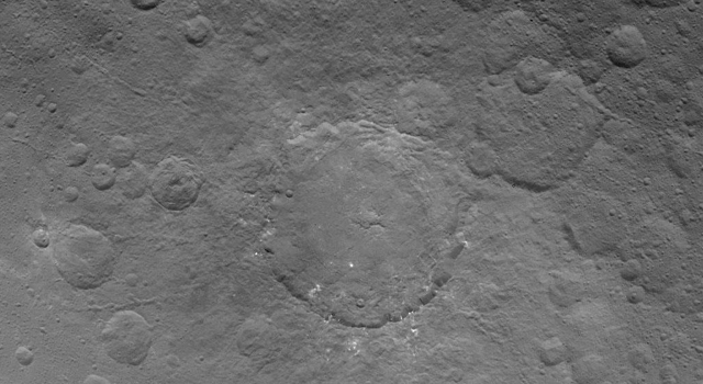 This image, taken by NASA's Dawn spacecraft on June 24, 2015, shows Dantu crater on dwarf planet Ceres from an altitude of 2,700 miles (4,400 kilometers); Dantu crater as small patches of bright material sprinkled around it.