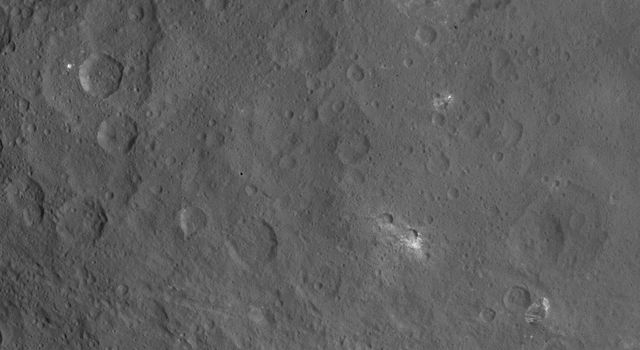 This image of Ceres, taken by NASA's Dawn spacecraft, features a large, steep-sided mountain and several intriguing bright spots. The mountain's height is estimated to be about 4 miles (6 kilometers). It is the highest point seen on Ceres so far.