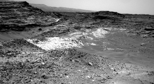 The Martian outcrop where pale rock meets darker overlying rock near the middle of this view from NASA's Curiosity Mars rover is an example of a geological contact. It was taken with the rover's Navcam on May 21, 2015.