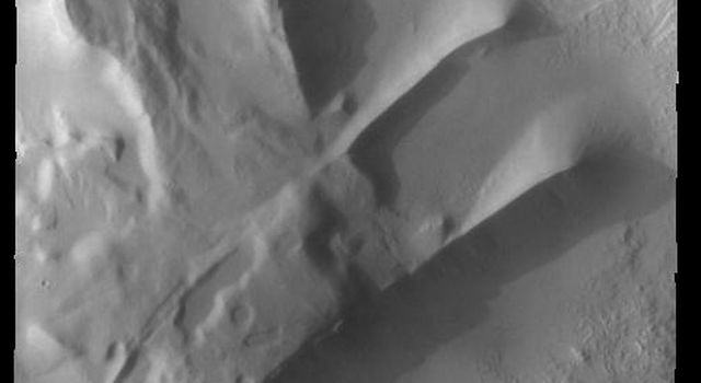 This image captured by NASA's 2001 Mars Odyssey spacecraft shows part of Cavi Angusti, a region of depressions near the south polar cap. The linear ridges in the image were likely formed by tectonic activity.