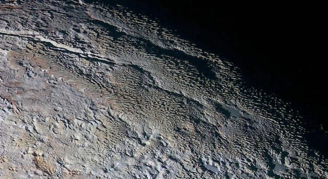 In this extended color image of Pluto taken by NASA's New Horizons spacecraft, rounded and bizarrely textured mountains, informally named the Tartarus Dorsa.