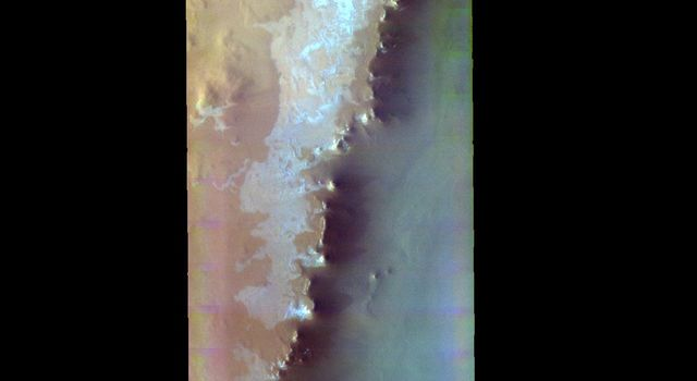 The THEMIS VIS camera contains 5 filters. The data from different filters can be combined in multiple ways to create a false color image. This image from NASA's 2001 Mars Odyssey spacecraft shows part of the mesa that Escorial Crater is located on.