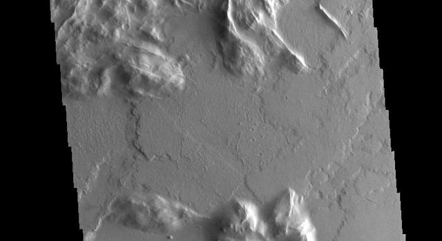 Located southwest of Olympus Mons, this image captured by NASA's 2001 Mars Odyssey spacecraft shows part of a complex region that has undergone several geologic processes.