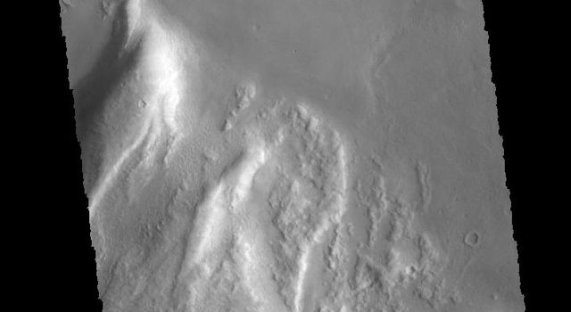 This image from NASA's 2001 Mars Odyssey spacecraft shows the northern margin of Tanaica Montes. These hills are cut by fractures, which are in alignment with the regional trend of tectonic faulting found east of Alba Mons.