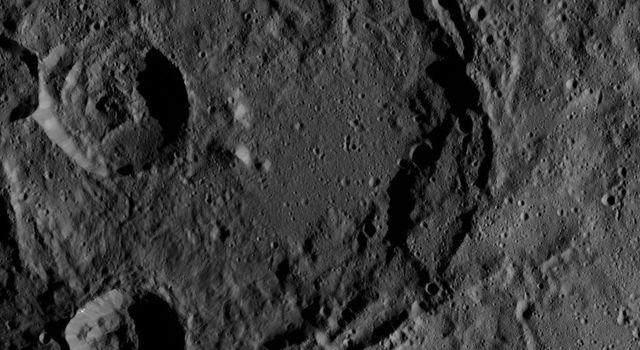 This image of Ceres, taken by NASA's Dawn spacecraft, shows a giant, ancient impact crater with smaller craters in its interior. The large crater shows partial terracing on its southeast rim, whereas the north part is almost fully degraded.