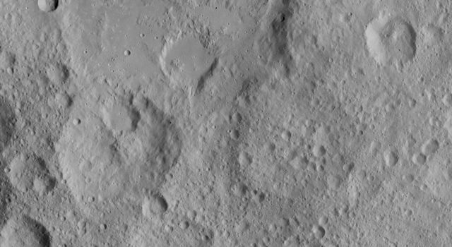 This image from NASA's Dawn spacecraft shows cratered terrain in the northern hemisphere of Ceres. Ikapati crater (top) appears with several flat plains filled by flows, smooth material and ejecta from the crater interior.