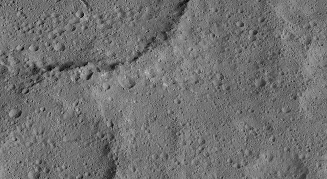 This view of Ezinu Crater on Ceres was taken by NASA's Dawn spacecraft on Oct. 19, 2015. Ezinu is the large crater in the top left corner of the image and contains a canyon-like feature near its center.