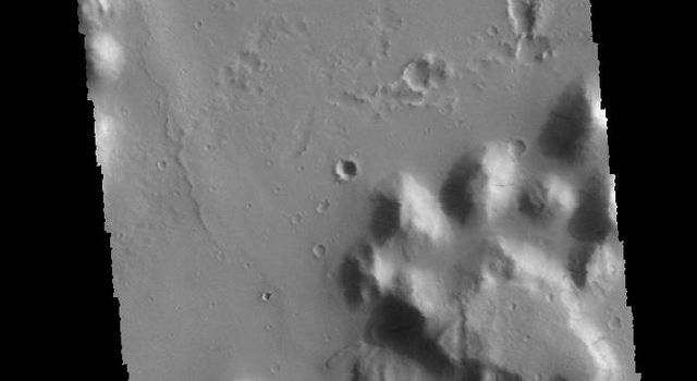 This image captured by NASA's 2001 Mars Odyssey spacecraft shows dark slope streaks on several small mesas in Amazonis Planitia.