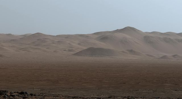 "This early-morning view from NASA's Curiosity Mars rover covers a field of view of about 130 degrees of the inner wall of Gale Crater. The rover's location was on the ""Naukluft Plateau"" of lower Mount Sharp."
