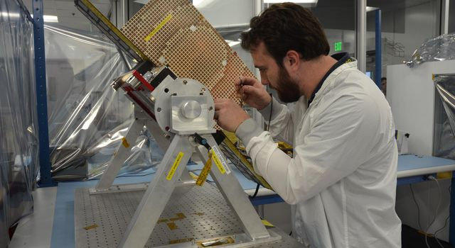 Engineers for NASA's MarCO (Mars Cube One) technology demonstration inspect one of the two MarCO CubeSats. Joel Steinkraus, MarCO lead mechanical engineer, left, and Andy Klesh, MarCO chief engineer, are on the team at NASA's Jet Propulsion Laboratory.