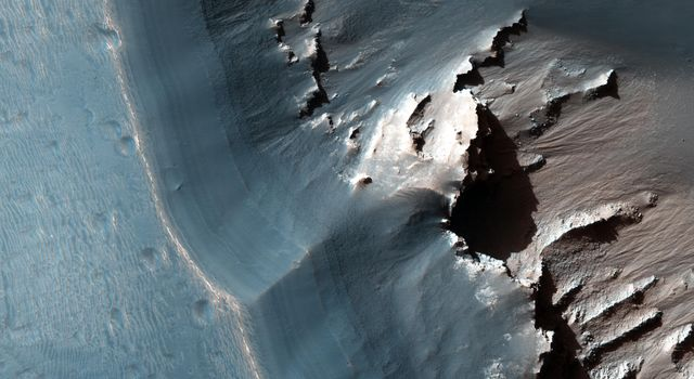 This image, captured by NASA's Mars Reconnaissance Orbiter spacecraft, shows the western side of an elongated pit depression in eastern Noctis Labyrinthus. Along the pit's upper wall is a light-toned layered deposit.