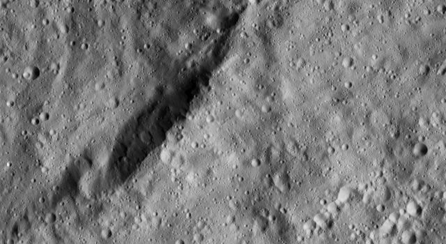 The view from NASA's Dawn spacecraft shows an unnamed crater that lies in the northeast part of the larger impact feature Gaue. The area is dominated by small craters and is relatively smooth in general.