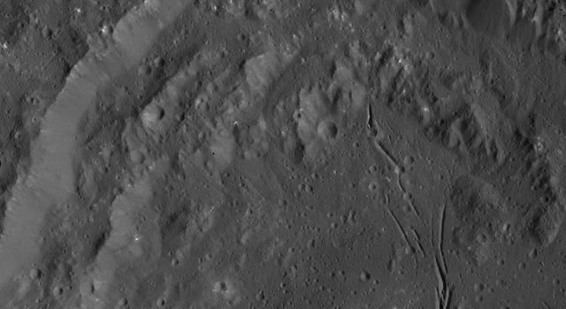 NASA's Dawn spacecraft obtained this view of Azacca Crater on Ceres. The rim of this crater has terraces descending from its rim down to its floor. The crater's floor is relatively free of large impact scars and is named for the Haitian god of agriculture